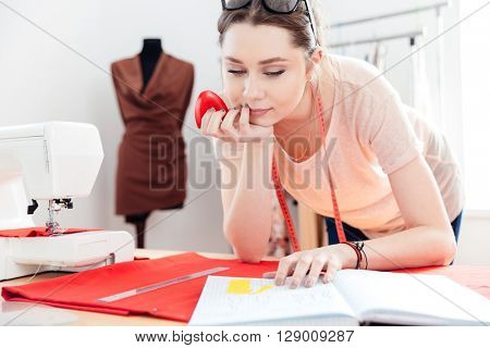Concentrated beautiful young woman seamstress using pattern and drawing on red fabric in workshop