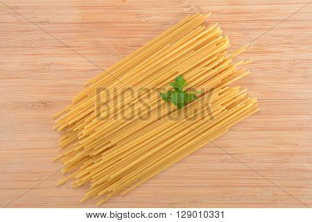 uncooked pasta noodles on butcher block background