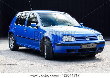 KRIVOY ROG, UKRAINE - APR 23- Blue Volkswagen Golf hatchback standing on a the asphalt in sunlight, Saturday 23 April 2016