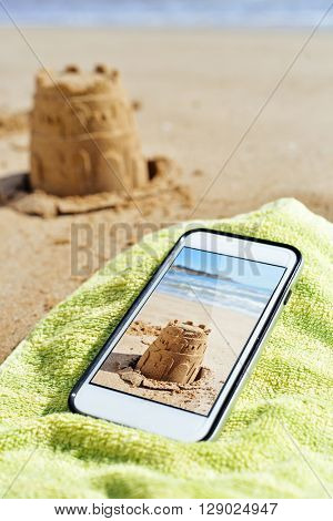 a smartphone with a picture shot by myself of a sandcastle in its screen, placed on a green towel on the sand of a beach and the depicted sandcastle in the background