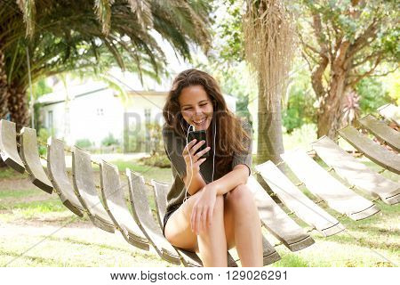 Happy Young Woman Sitting In Hammock Listening To Music