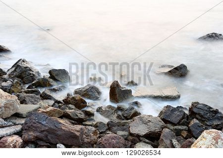 Sea mist softness of the tides and sunset at evening with rocks in foregroundviewpoint in Chanthaburi Thailand.