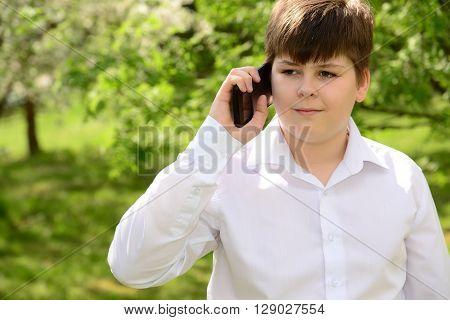 Teen boy talking on the phone outdoors