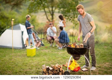 Guy put firewood in grill in campground
