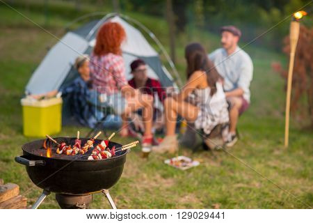 Evening in campground, close up of grill with skewers in forest