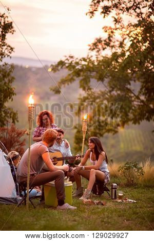 Guys and lassies talk and play guitar at twilight in campground in nature