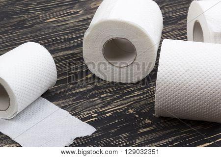 Rolls of toilet paper on black  wooden board