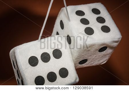 Pair of white plush dices hanging on a string with the brown background