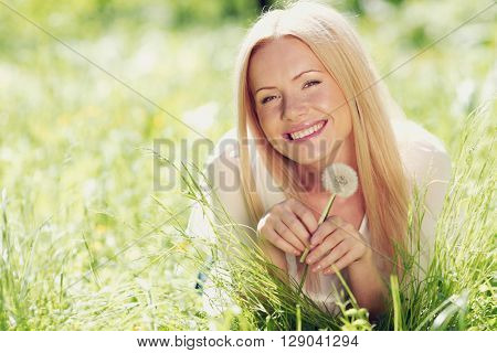 Beautiful young woman with dandelion flower lying on summer meadow