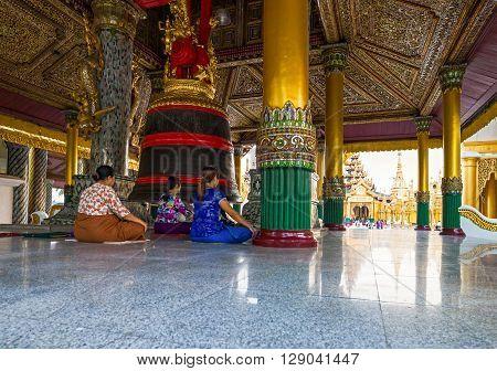 Yangon Myanmar - January 9 2012: Religious in prayer in the Swedagon Pagoda.