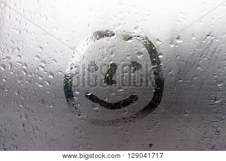 Smile on the misted window in the summer