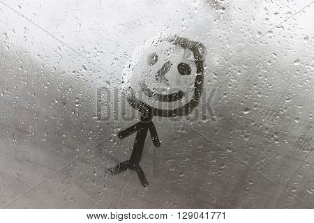 The human figure on the misted window