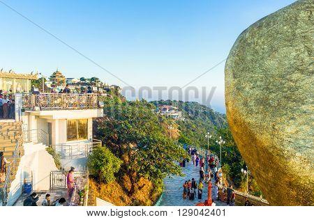 Kyaikhto Myanmar - January 10 2012: Religious local people near the delicately balanced golden Stupa on the sacred Buddhist mountain