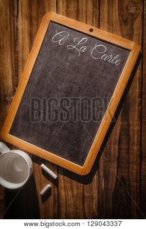 A la carte message against chalkboard on desk