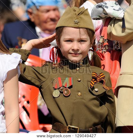 Orel Russia - May 9 2016: Celebration of 71th anniversary of the Victory Day (WWII). Little girl saluting in Russian military uniform with medals and St.George ribbon closeup