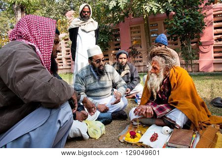 BODHGAYA, INDIA - JAN 8, 2013: Conversation of the Muslim people with one hindu man about religion on January 8, 2013. Bodhgaya is a place of pilgrimage. Siddhartha Gautama attained enlightenment here at 500BC