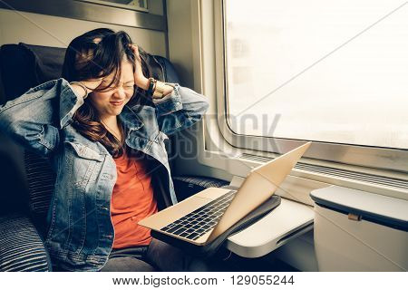 Asian college girl frustrated with laptop on the train warm light tone with copy space
