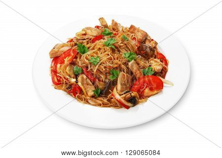 Asian food. Fried Thai glass Rice noodles with meat and vegetables. Chinese transparent glass rice vermicelli fried with meat, parsley and tomatoes. Korean funchoza cellophane noodles.
