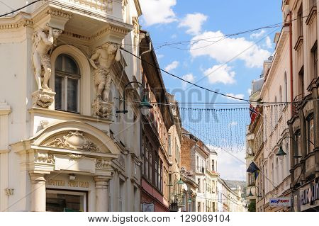 SARAJEVO BOSNIA AND HERZEGOVINA - SEPTEMBER 4 2009: Two atlantes supporting a balcony above the entrance to the pharmacy on the corner of Ferhadija street and Fra Grge Martica square.