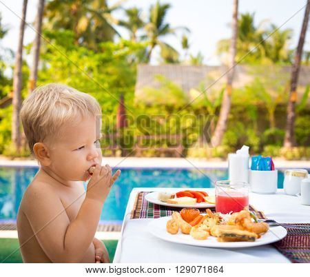 Child has a breakfast near a swimming pool