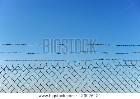 chainlink fence against blue sky, design background