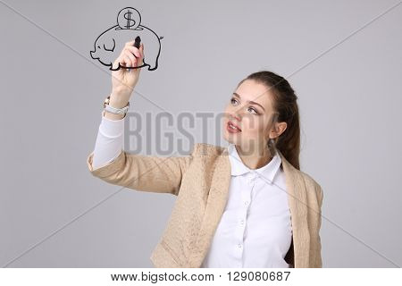 young woman drawing a piggy Bank