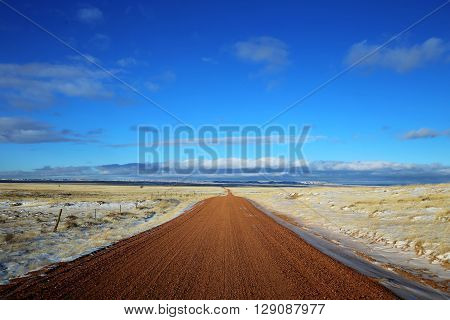Lonely dirt road through snowy plains with mountains in background