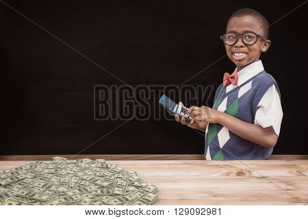 Cute pupil with calculator against blackboard on wall