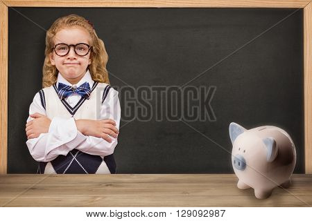 Cute pupil with arms crossed against piggy bank