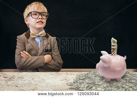 Cute pupil dressed up as teacher against blackboard on wall