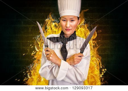 Confident female cook holding knives in kitchen against green background with vignette