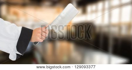 Composite image of chef hand holding a knife against a blurred background