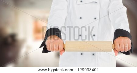 Close up on a chef holding a rolling pin against kitchen in a stylish home