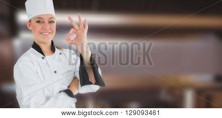 Happy female chef gesturing ok sign against pots and pans on stove top