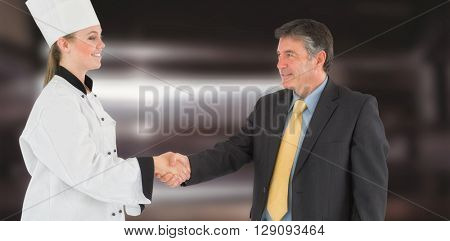 Businessman and female chef shaking hands against deep fat fryers