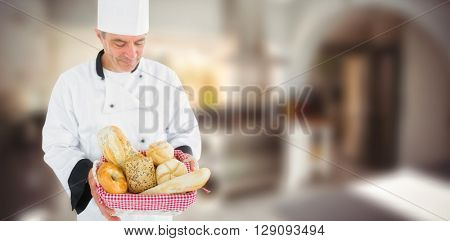 Composite image of friendly chef holding a bread basket on a blurred background