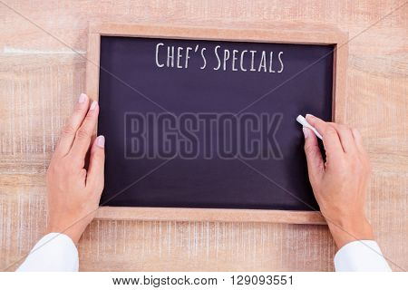 Composite image of chef writing on a blackboard on a wooden desk