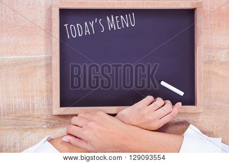 Composite image of hight angle of hand chef with blackboard on a wooden desk