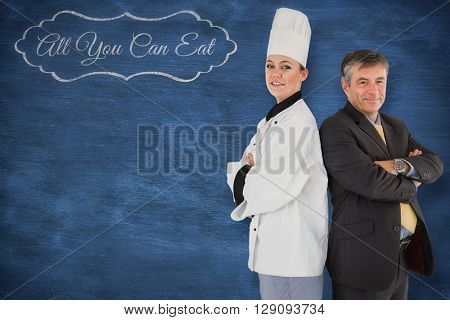 A cook posing with a businessman against blue chalkboard