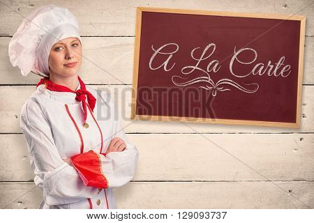 Pretty chef standing with arms crossed against white wood