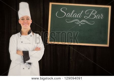 Composite image of friendly woman chef smiling and crossed arms against a wooden background