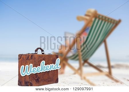 Woman in sunhat sitting on beach in deck chair using tablet pc against weekend message on an old suitcase