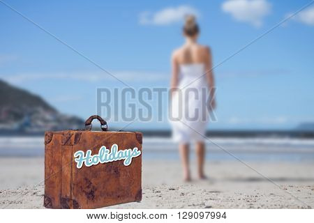 Blonde in white dress walking on the beach against suitcase with the message holidays