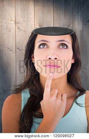 Pretty brunette looking up thoughfully against bleached wooden planks background