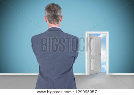 Rear view of businessman against open door on green wall