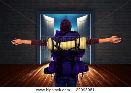 Rear view of a hipster woman with arms outstretched against open big door on wall
