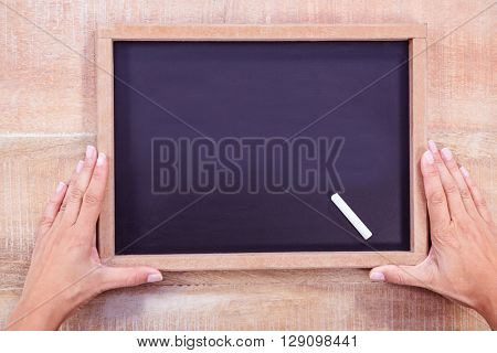 Composite image of hand holding a chalkboard on a wooden desk