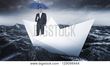 Businessman smiling at camera and holding blue umbrella against paper boat floating on the sea