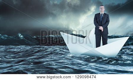 Mature businessman looking at camera against paper boat floating on the sea