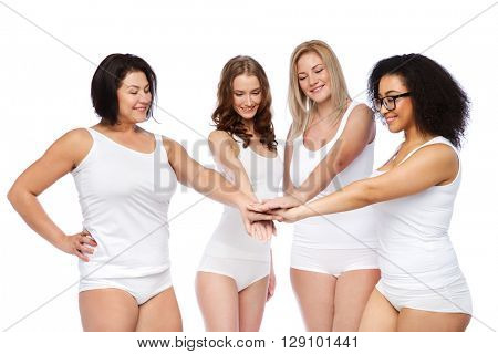 gesture, friendship, beauty, body positive and people concept - group of happy different women in white underwear holding hands together on top